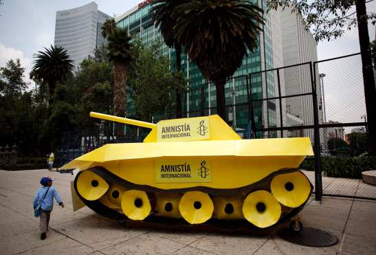 A child walks around a fake tank parked outside the U.S. embassy during a protest held by Amnesty International in Mexico City