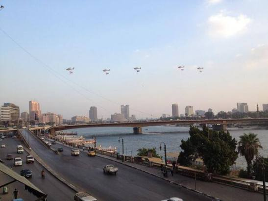 Military helicopters fly over protestors with Egyptian flags