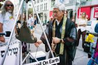 Rev. Earl Ikeda of the NYC Buddhist Church rings the peace bell in Union Square Park Photo (c) Joan Roth