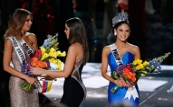 Former Miss Universe Paulina Vega, center, takes away the flowers and sash from Miss Colombia Ariadna Gutierrez, left, before giving it to Miss Philippines Pia Alonzo Wurtzbach, right, at the Miss Universe pageant Sunday, Dec. 20, 2015, in Las Vegas. According to the pageant, a misreading led the announcer to read Miss Colombia Ariadna Gutierrez as the winner before they took it away and gave it to Miss Philippines.(AP Photo/John Locher)