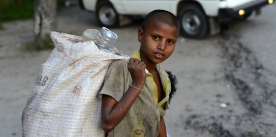 A young Indian ragpicker looka on as he collects used mineral water bottles in Siliguri on June 12, 2013, on World Day Against Child Labour. The International Labour Organization (ILO) launched the first World Day Against Child Labour in 2002 as a way to highlight the plight of children engaged in work that deprives them of adequate education, health, leisure and basic freedoms, violating their rights. AFP PHOTO/Diptendu DUTTA (Photo credit should read DIPTENDU DUTTA/AFP/Getty Images)